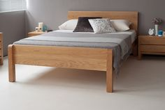 Tibet contemporary wooden bed with footboard from Natural Bed Company. The chunky Tibet bed is shown here in solid oak with contemporary grey bedding against a warm grey wall. www.naturalbedcompany.co.uk. Feel free to pin!