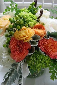 love the curly roses in the arrangement and the little fern-like greenery