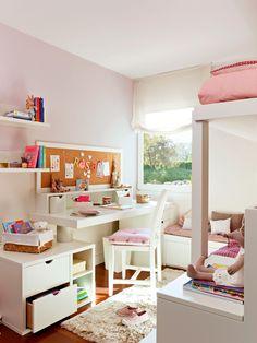 Zona de estudio en habitación infantil con pared rosa y muebles en blanco, con soluciones de almacenaje, corcho para colgar notas, estanterías y alfombra_327770