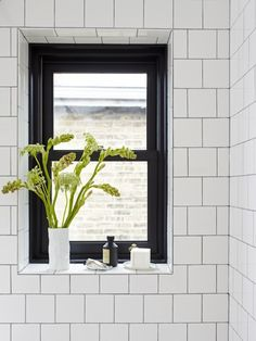 black window frame, square-cut tiles laid in a brick pattern, charcoal grout.