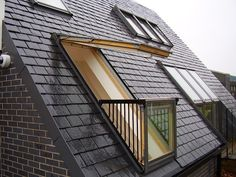 property with black slate roof and open skylight