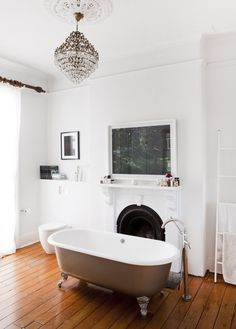 AMAZING enormous bathroom which used to be a bedroom. Clawfoot bath, chandelier, original fireplace, timber floorboards -you can't go wrong! 'I loved the idea of a chandelier in the bathroom, this one is from Russia I believe'. says Nicola. Photograph above the fireplace by The Reindorf's dear friend Toby Burrows.Photo – Jason Busch, production – Lucy Feagins / The Design Files.