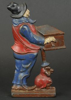 ORGAN GRINDER DOORSTOP 	      	                 Two sided casting depicts organ grinder with monkey performer holding change cup. 10 h. x 6.