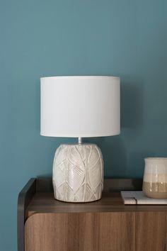 Si buscas una lámpara blanca pero no quieres que sea minimalista esta es tu lámpara. Tiene una base de cemento blanco roto con una preciosa textura de hojas y una tulipa de tela de tela de color blanco, ideal para espacios en los que predominen los colores claro o cuando no quieras que la lámpara se convierta en el centro de atención.  Su diseño es sencillo pero con personalidad encajará perfectamente en tu salón, en las mesitas o cómoda de tu dormitorio o en tu vestíbulo. #rderoom #lampara