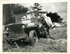 """1944- Jeep converted into fire truck at U.S. Coast Guard Air Station in Elizabeth City, North Carolina, carries men in """"Men from Mars"""" suits through field to scene of crash."""