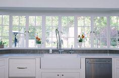 White kitchen with garden view cabinetsanddesigns.net