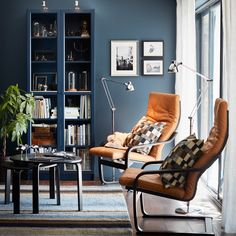 A small livingroom furnished with two armchairs with natural-coloured leather cushions and black-brown bent beech frames. Shown together with two small black tables and a dark blue glass door cabinet filled with books.