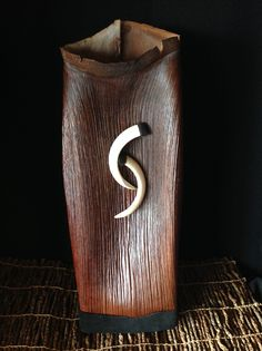 """""""Achieving Balance"""" A striking contemporary, sculptural piece. Natural Alexander Palm sheath body with natural edge collar, wood base, waxed linen stitching and wild Hawaiian boar tusks. Approx. 17"""" high, 6"""" wide, 4"""" deep. Price range $585"""