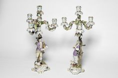 A Pair of Meissen Porcelain Figural Table Candelabra, circa 1870, fashioned as two musicians, she stands playing the recorder, a sheep at her feet by a leafy tree trunk, he stands playing pipes, a dog at his feet, on rocaille scroll form bases, with candlestick nozzles supporting three-branch four-light candle brackets encrusted with a profusion of flowers, in typical colours and gilt throughout,