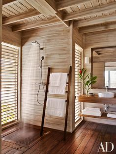 Sheathed in American pine, a guest bath is equipped with Hansgrohe shower and sink fittings.