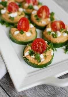 Cucumber Hummus Bites make the perfect finger food and appetizer for your next part or get together. Cucumbers are topped with hummus, tomatoes and feta.