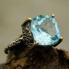 Square faceted blue topaz ring in silver bezel and brass prongs setting with sterling silver texture oxidized band