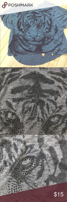 """Tiger shirt with rhinestones and """"claw"""" rip detail Lightweight, gray stretchy fabric is super soft! The tiger image is a black graphic with black rhinestone details surrounding the tiger's eyes. Small, round holes (about 1 in. diameter) are grouped on both the front and back of the shirt as tiger claw rip details. Wear with a bandeau to show a little skin. Wear with jeans for a casual look or add heels for a sexy outfit. This is a size small, but has a loose fit, so it can fit a medium too…"""