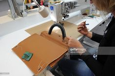 An employee works on a Hermes Kelly bag at the Maroquinerie de la Tardoire, a Hermes workshop specialized in products made with calfskin, in Montbron, southwestern France, on June 11, 2015.