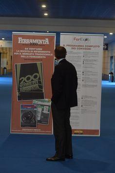 Un visitatore legge i manifesti esposti in fiera. A destra quello con il programma dei convegni: sponsor Nobex.