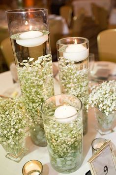 Rustic centerpieces that aren't mason jars. Baby's breath in cylinder vases and floating candles. http://www.theweddingguru.ca/rustic-centerpieces-arent-mason-jars/ #rustic #rusticcenterpiece