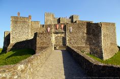 The King's Gate Barbican Causeway, Dover Castle, Kent, England, United Kingdom. Behind the North Barbican on the right are the flat-topped King's Gate flanking towers. Inner Curtain Wall gateway opens into Keep Yard and Henry II's Great Tower (with flag). View from pier at end of stone bridge above tunnel to St John's Tower and the Ravelin. Norman Listed Building, English Heritage, and Scheduled Ancient Monument. Medieval History, Travel, and Tourism. See: http://www.panoramio.com/photo/87684817