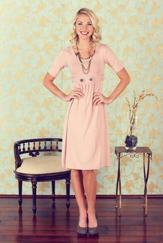 "Modest Dresses: Bailey Dress in Pink  The Bailey is a twist on the Mikarose ""Ashley"" dress. If you were a fan of the Ashley, you will love this dress. The basic half-sleeve complements any shape, and helps draw your eye to the detail on the dress. The waistband has 2 plackets that cross over each other and button in the front. The gathering on the front is also very flattering. You will feel extremely cute and confident in the Bailey! $49.99 http://www.jenclothing.com/mi-9001-bailey-pink.html"