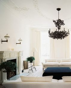 Elegant Living Room Decor with White Wall Paint Color and White Fabric Sofa Idea and Black Ottoman Set also Black Chandelier Lights and Modern Stacked Stone Fire Place and White Curtains Home Interior, Interior Architecture, Interior And Exterior, Interior Design, Interior Livingroom, Luxury Interior, Living Room Designs, Living Room Decor, Living Spaces