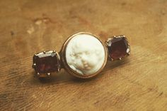 A tiny white glass cherub cameo pin flanked by two foiled garnets and dating to 1820. DM for details & price #antique #cameo #georgian #garnet #pin