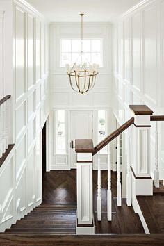 Chic two story foyer features walls clad in decorative trim moldings illuminated by a brass Lancaster Chandelier.