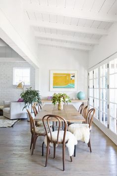 Isn't this space stunning? White washed ceilings, fur throws on the chairs and a long sociable table - the perfect dining area.
