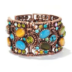 Add some eclectic, noticeable style to your ensemble with this copper and crystal cuff bracelet. Created with a 1950s retro look, this outstanding piece of jewelry features glass cats eye turquoise, yellow, and green ovals with crystal accents.