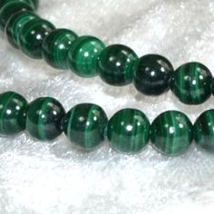 """Malachite energies: Love, Money, Protection. It is believed to be a strong protector of children. It is said to protect the wearer from accidents and protects travelers. It aids success in business and protects against undesirable business associations. It is a stone of balance in relationships. To help get rid of nightmares, keep a piece in your bedroom. It should not be used for physical healing. It has been called the """"mirror of the soul"""". It reflects what is there, negative or positive."""
