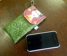 Capa para celular confeccionada com tecidos nacionais, acolchoada com manta acrílica e quilt. <br>Possui uma alcinha lateral com uma argola e um mosquetão.