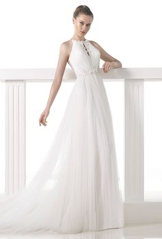 Brides: Pronovias. Flared halter dress in tulle with front opening. Gemstone embroidery appliqués with floral details at the waist and neck. Sheer back decorated with gemstone embroidery and gauze flowers.