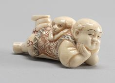 Polychrome carved ivory netsuke in the form of a sleeping child with a puppy lying on his back, Japan