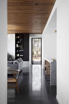 This modern house interior features a Blackbutt shiplap ceiling and burnished concrete flooring.