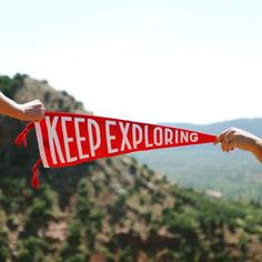 "American-made felt pennant produced and printed by Oxford Pennant. Bold block lettering ideal for inspiring daily adventure from close or afar. Dimensions // 9"" x 27"" Color // Red with White Ink"