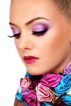 Portrait of a female face with violet make up and artificial roses over her neck