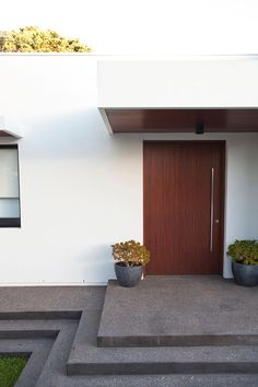The dark wood door leading into this Australian home has vertical lines and a tall, thin, vertically placed minimalist metal door handle follows the lines in the wood.
