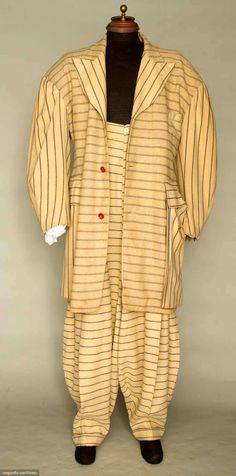 1938-1942 zoot suit: 2 different pattern striped wools, long fitted coat, oversize padded shoulders & exterior pouch pockets, red plastic buttons, high-waist balloon pants, pegged cuffs, 4 slash pockets, crudely made suspenders in cinnamon wool.  Sold at auction for $ 78,000