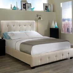 Wood platform bed with tufted taupe upholstery and foam cushioning.    Product: BedConstruction Material: Wood...
