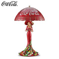 "Classic COCA-COLA Girl Louis Comfort Tiffany-Inspired Lamp The Timeless Taste Of COCA-COLA Accent Lamp Limited-edition COCA-COLA® lamp inspired by stained-glass lamps of Louis Comfort Tiffany. Features COCA-COLA logo and vintage COKE® glass. Measures 12"" H  Price: $125.00"