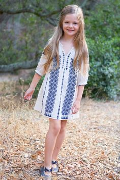 This light and airy white girls' dress projects a sense of sweet innocence and is decorated with bands of an intricate navy Moroccan pattern with printed tassels at the hem, giving the dress a vintage bohemian feel. Sleeves feature stretchy elastic cuffs with ruffle embellishment Open V-neck neckline Designed by Pink Chicken