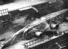 The SS Normandie burns and capsizes at the dock in NYC while being refitted as a troop carrier.