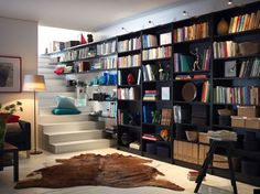 Ikea library. Take back of book shelves off. Replace with reclaimed old wood. Put 4-5 shelves on large wall in living room behind chairs & lamp table