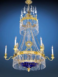 This Russian chandelier is distinguished by its exceptional rarity. The entirety of this important Neoclassical fixture is covered with a myriad of intricately cut glass lusters, all suspended from branches of hand-crafted ormolu. An elegant cobalt blue glass central bowl completes this engaging work of illuminated art.
