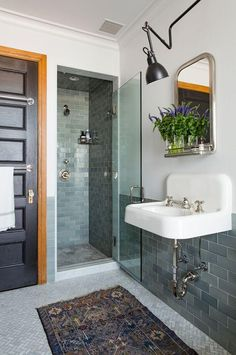 Love thie renovated townhouse bathroom with a soft cool color palette of sage green subway tiles, light gray herringbone tiles on the floor, floor to ceiling subway tiles in the shower, bright silver fixtures, and a black wall sconce and black painted door, paired with a vintage Persian runner rug.
