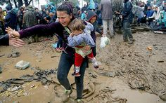 A Syrian refugee carries her baby as she walks through the mud to cross the border from Greece into FYROM during a rainstorm, near the Greek village of Idomeni,