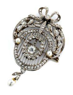 Länge: ca. 4,7 cm. Breite: ca. 2,5 cm. Gewicht: ca. 10 g. WG 750. Um 1900. Zarter dekorativer Anhänger mit kleinen Perlen, Diamantrosen und...