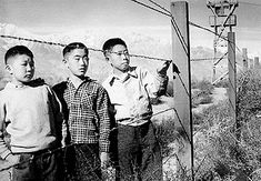 Japanese / American boys at an internment camp fence in the USA