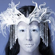 Snowqueen Leather Crown    Sculpted headdress in pearl white, accented with a faux opal stone and braided satin trim. The sides flare into abstract twists and curls, trimmed with snow white ostrich feathers. Dripping with freshwater pearls and Swarovski crystals, which shower the wearer's face and neck with rainbows and glimmers.