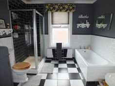 UNIQUE PERIOD HOME FOR SALE: THE BATHROOM ... wonderful proportions  style incorporating 4-piece suite: close coupled wc, wall mounted hand basin, panelled bath  separate fully tiled shower cubicle.  Striking monochrome decor is both elegant  contemporary - white brick tiling around the bath  lower walls complemented by dramatic black painted plaster walls above dado line. The black  white chess board effect tiled floor completes this capacious, functional and attractive FAMILY BATHROOM.