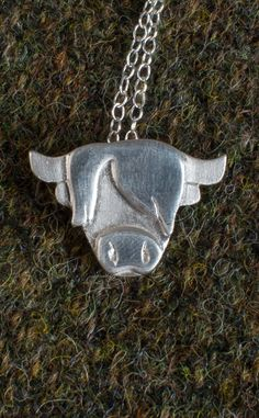 """- Handmade in Scotland - Provided with a 16"""", 18"""" or 20"""" sterling silver chain with spring ring clasp - Fine Silver facing - Sterling Silver chain  This silver Highland Coo necklace is hand cut and shaped in Scotland. The base has a brushed finish while the hair and nose are polished with a high shine - a truly luxurious handmade product."""