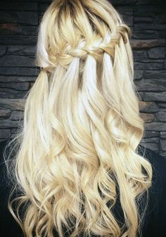 Curly tendrils add a fairy-tale feeling to this waterfall braided hairstyle.